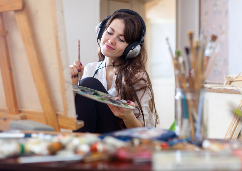 Long-haired woman in headphones  paints on canvas